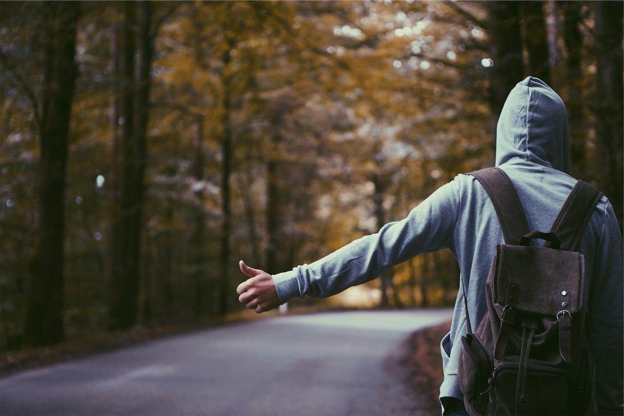 Stopár s ruksakom stojaci na ceste pri stromoch